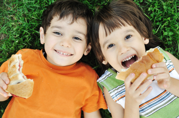 two-cute-boys-laying-on-ground-in-nature-and-happily-eating-healthy-food_21730-76