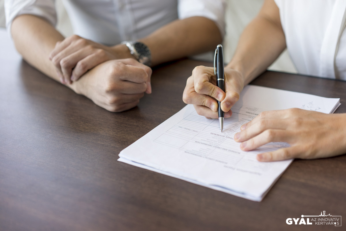 Hand of female hr manager filling in form at interview with male candidate. Close-up of young Caucasian businessman and businesswoman sitting at table. Woman writing in paper. Job interview concept