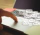 Composite image of hand using laptop put on a desk with letter icons