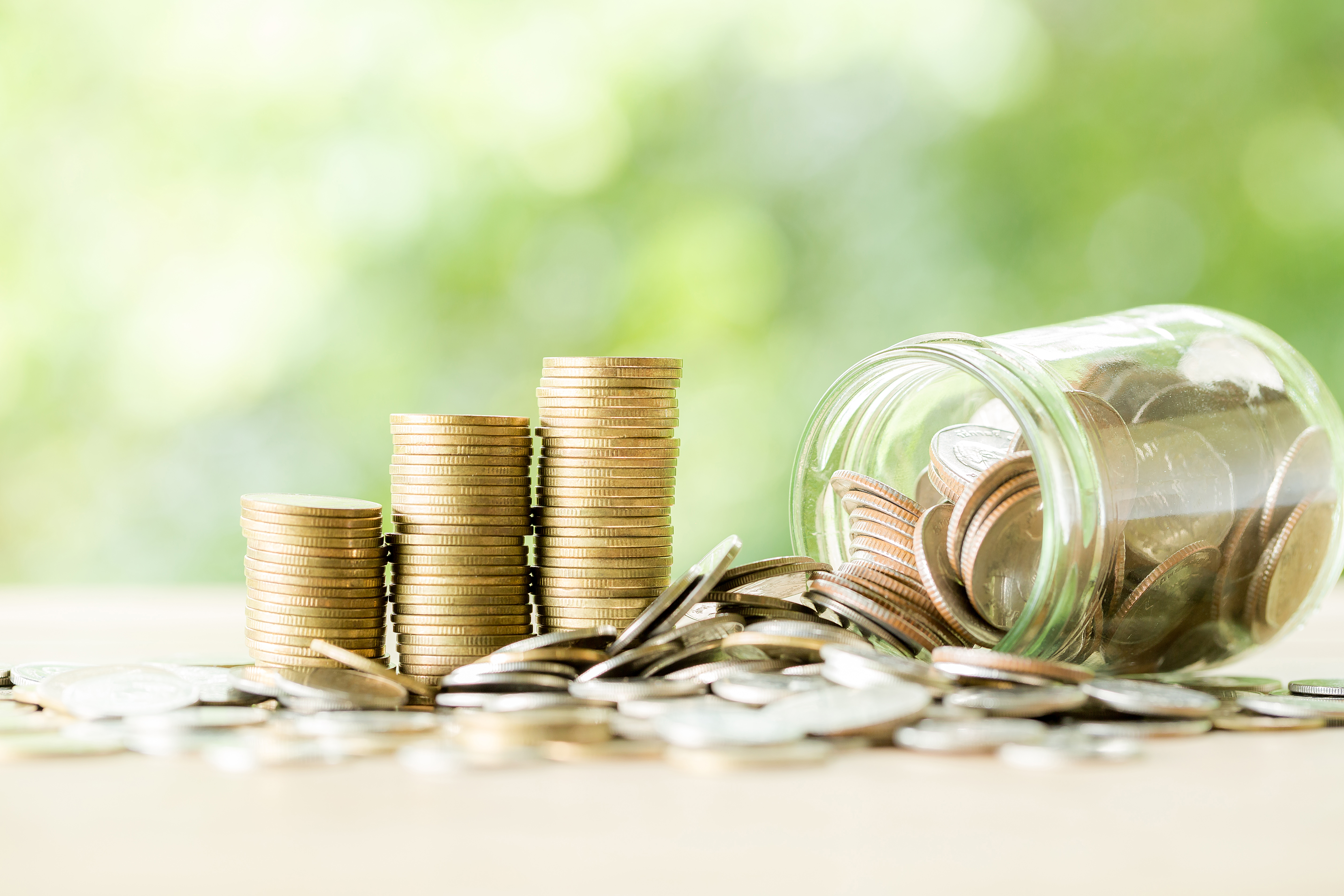 Coin on wooden table in front of green bokeh background. coins a concept of investment and saving moneys.